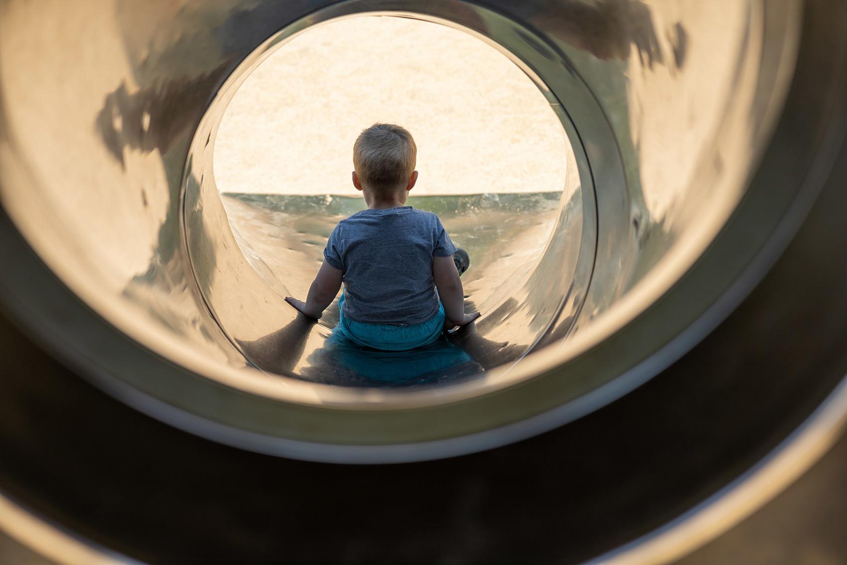 Ryggtavlan på en liten sittande pojke inuti en rutschkana