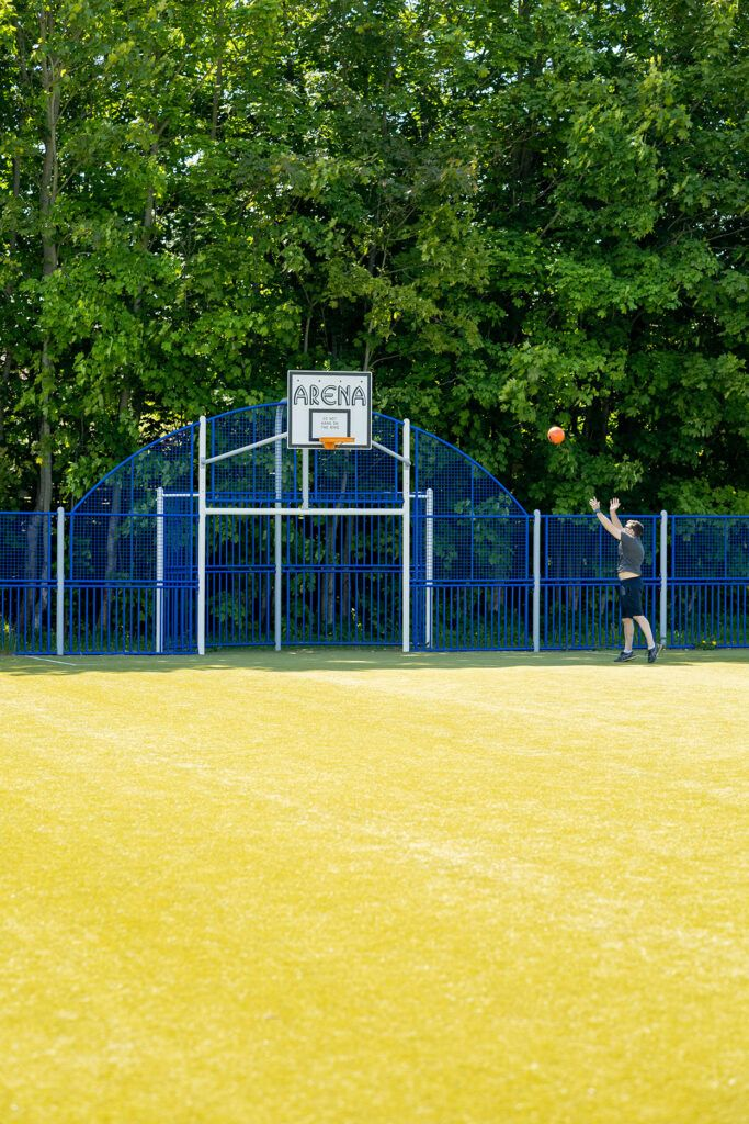 En man kastar en basketboll mot en korg på en inhängnad konstgräsplan