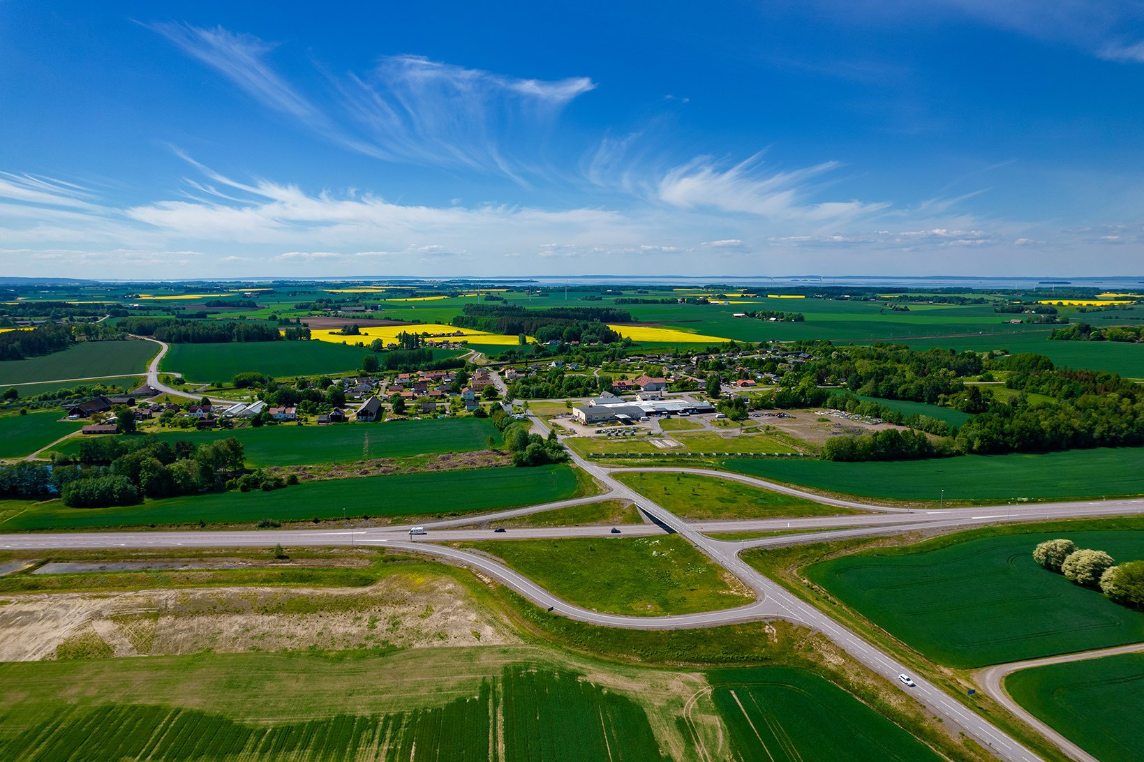 Drönarbild över ett slättlandskap, sommartid med gula rapsfält och väldigt blå himmel