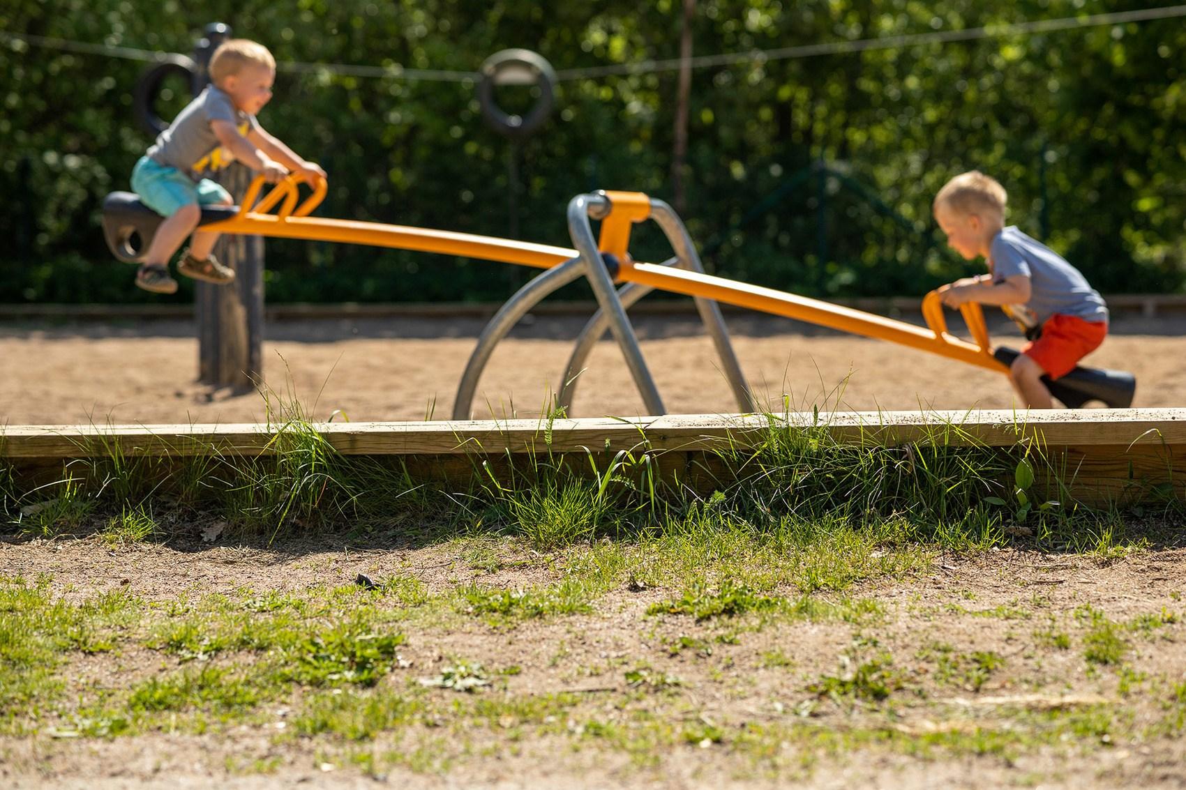 Två barn i en lekpark gungandes på varsin sida av en gul gungbräda