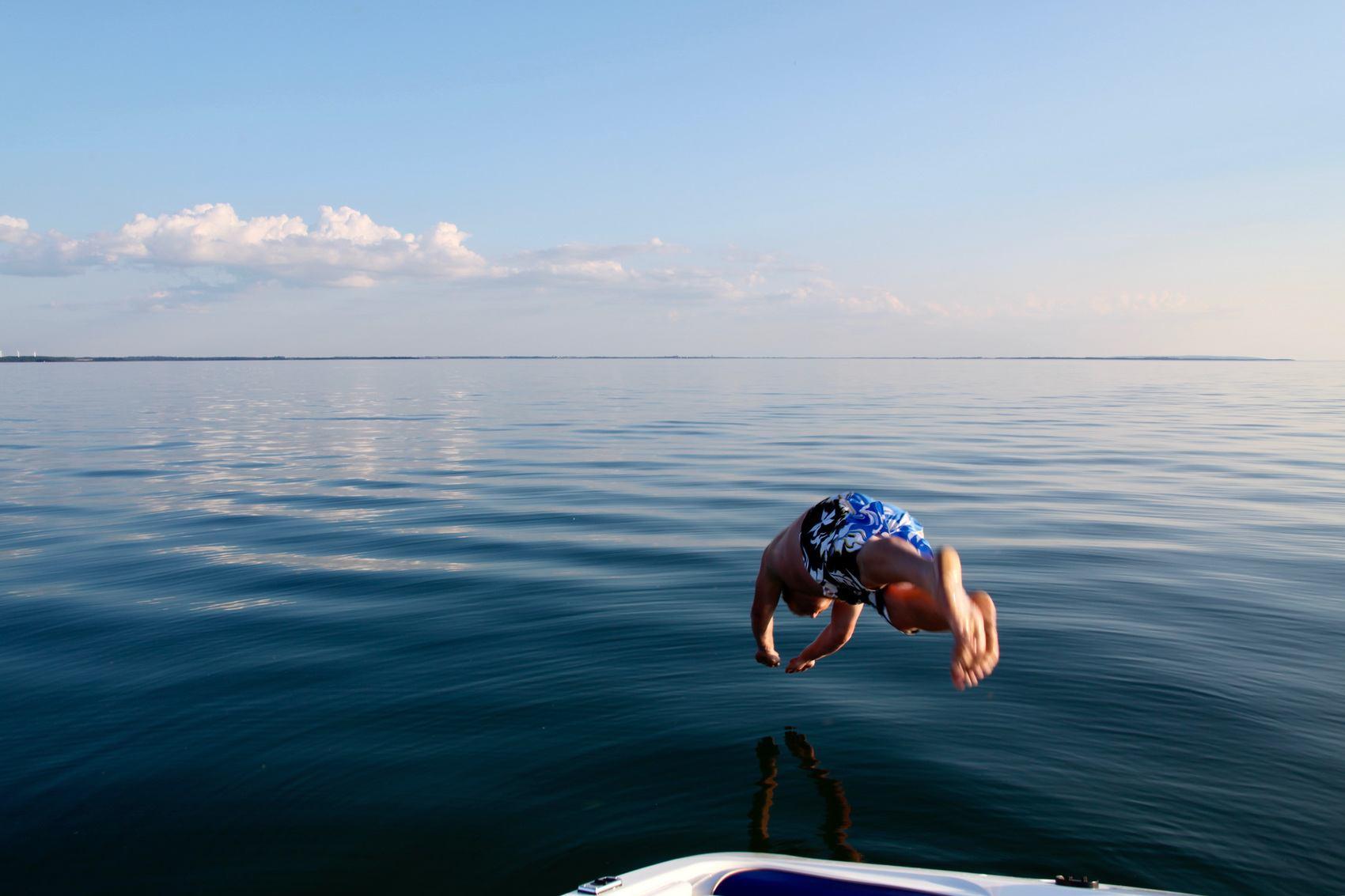 Man dyker i spegelblankt vatten från en båt