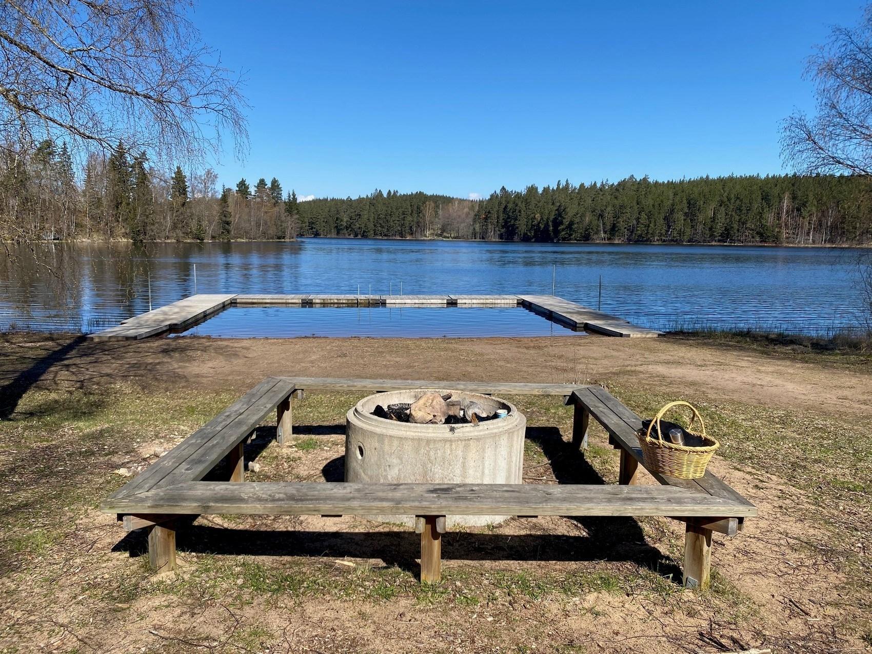 Grilllplats framför vatten med brygga