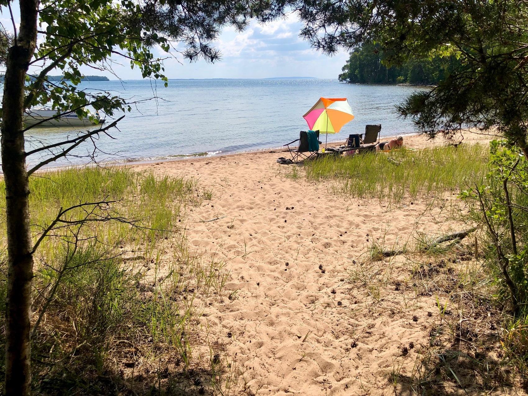 Foto från sandstrand. Vid strandkanten står två solstolar och ett färglatt parasoll.