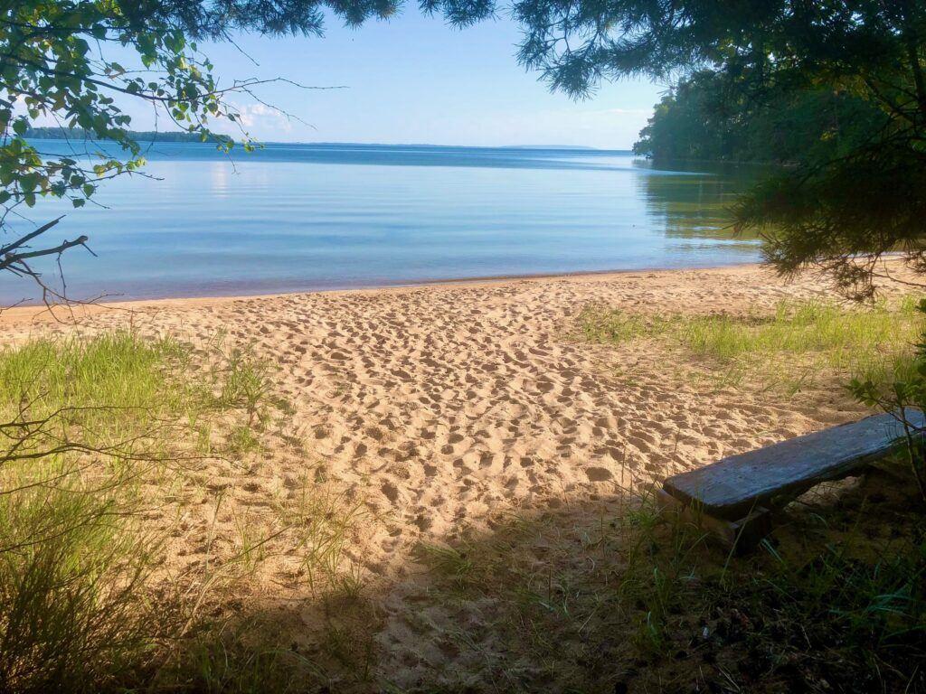 Vacker sandstrand en solig sommardag. Vattnet ligger helt stilla.