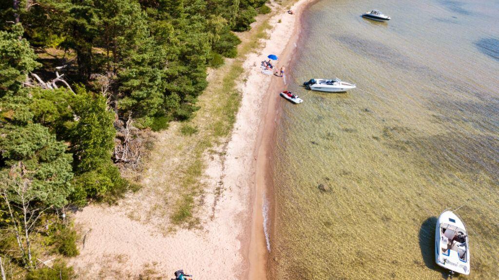 Drönarfoto över strandremsa. Vattnet är kristallklart och solen skiner.