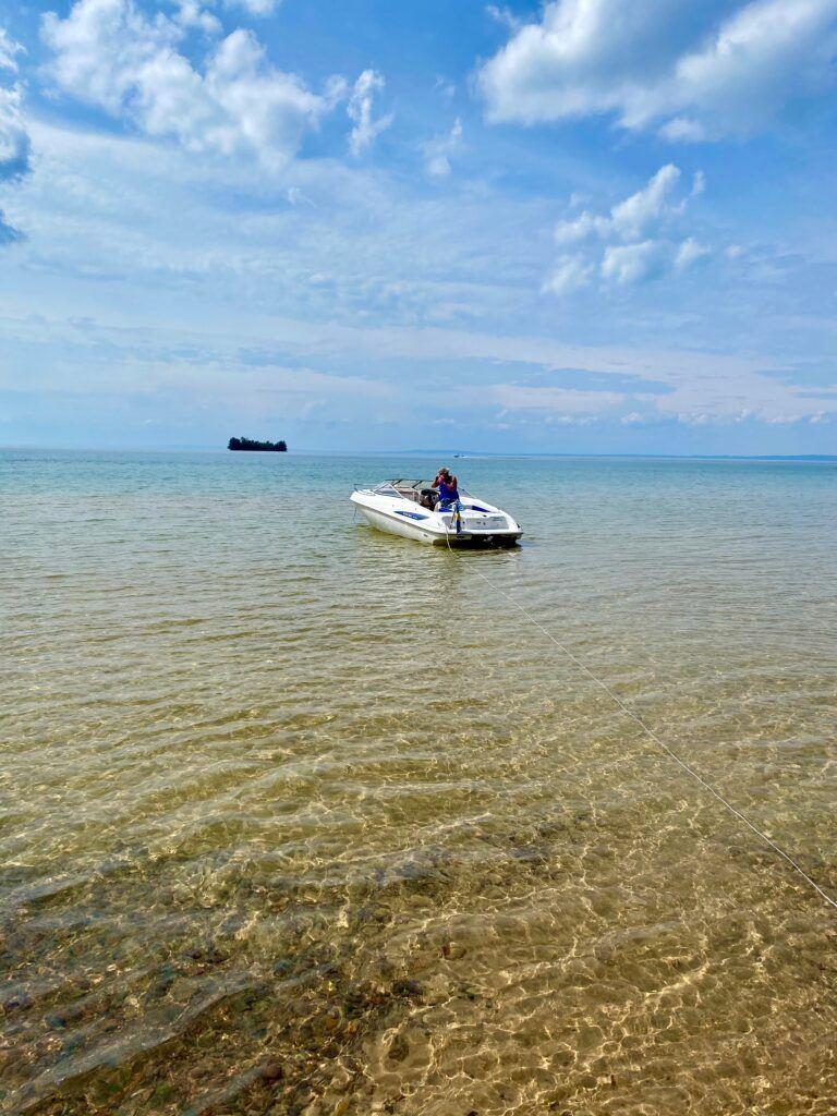 En motorbåt ligger och guppar i kristallklart vatten en vacker sommardag.