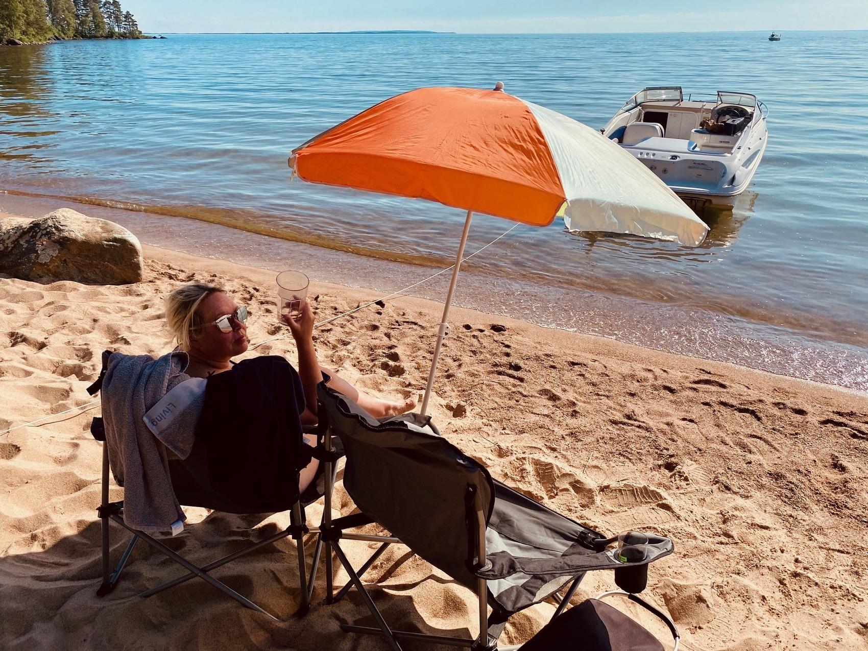 Kvinna sitter i solstol under parasoll på en solig sandstrand