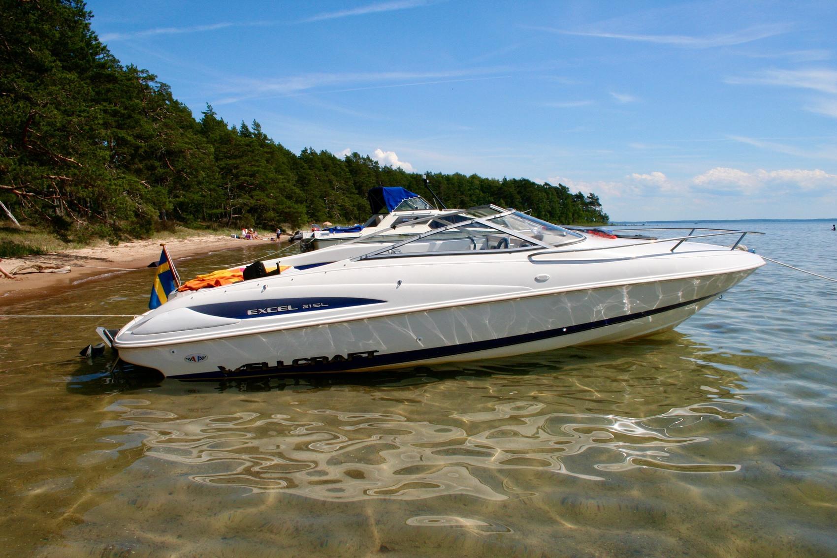 Motorbåt ligger förtöjd vid sandstrand