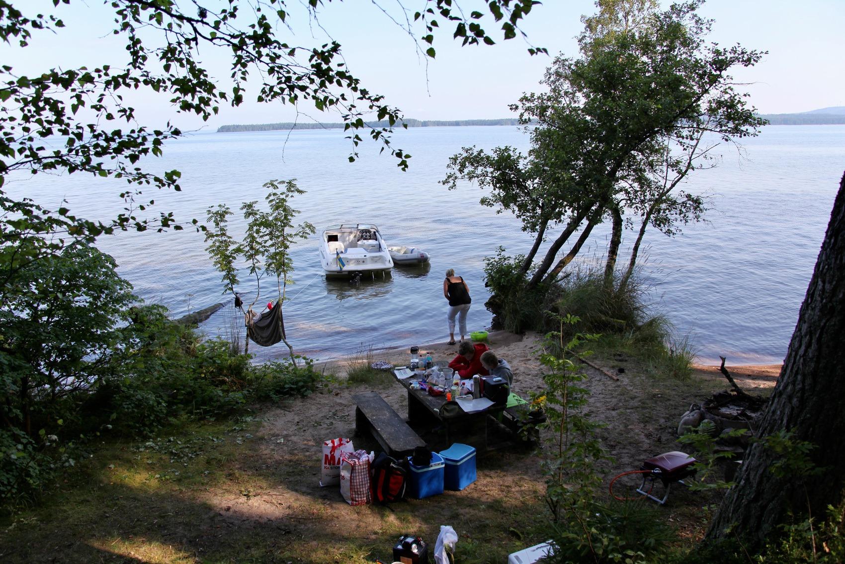 Strand där familj har slagit läger. Packning står på stranden och i vattnet lig