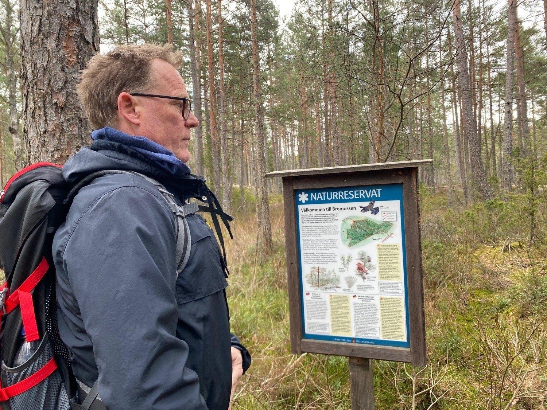 En man med vandringsryggsäck står och tittar på en skylt i skogen