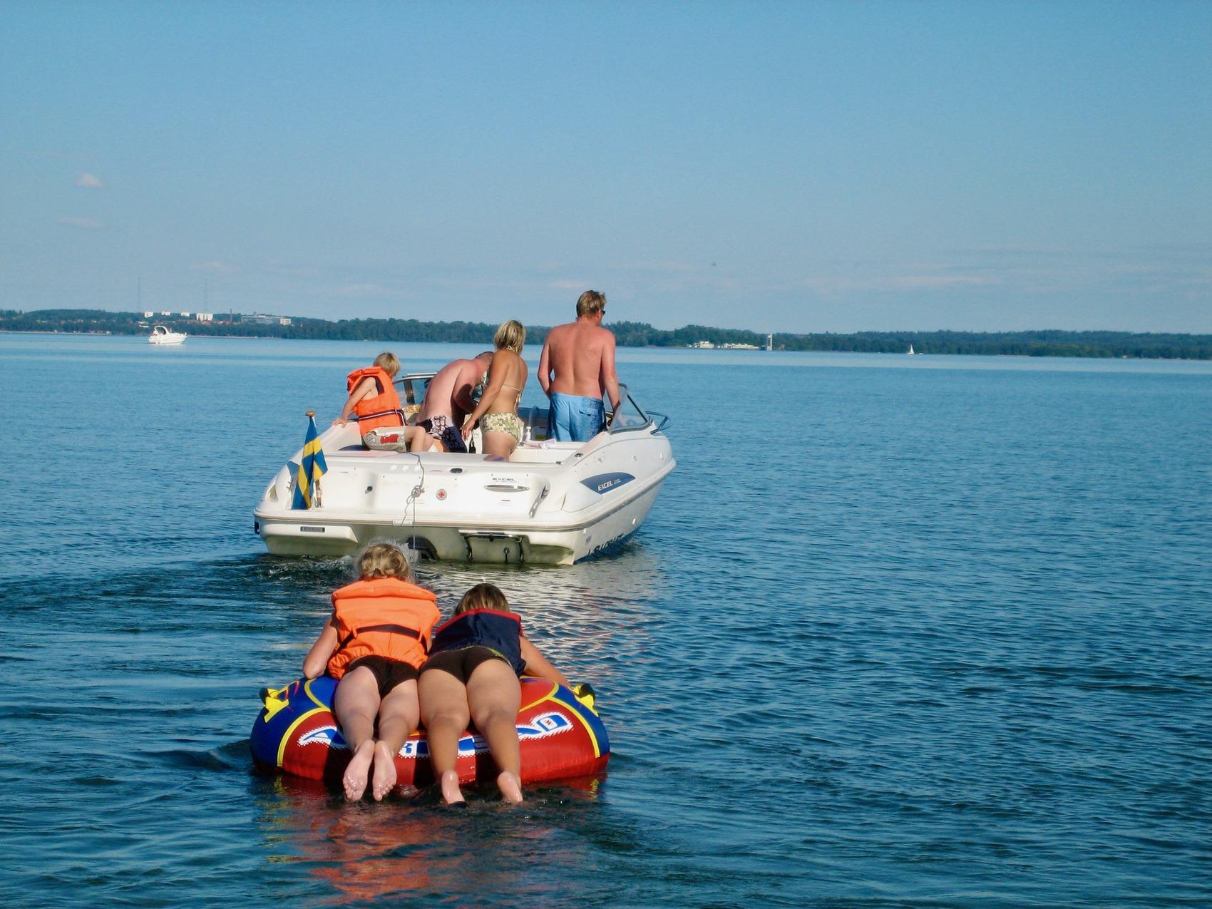 Barn ligger på mage på en flytande ring som åker efter en båt