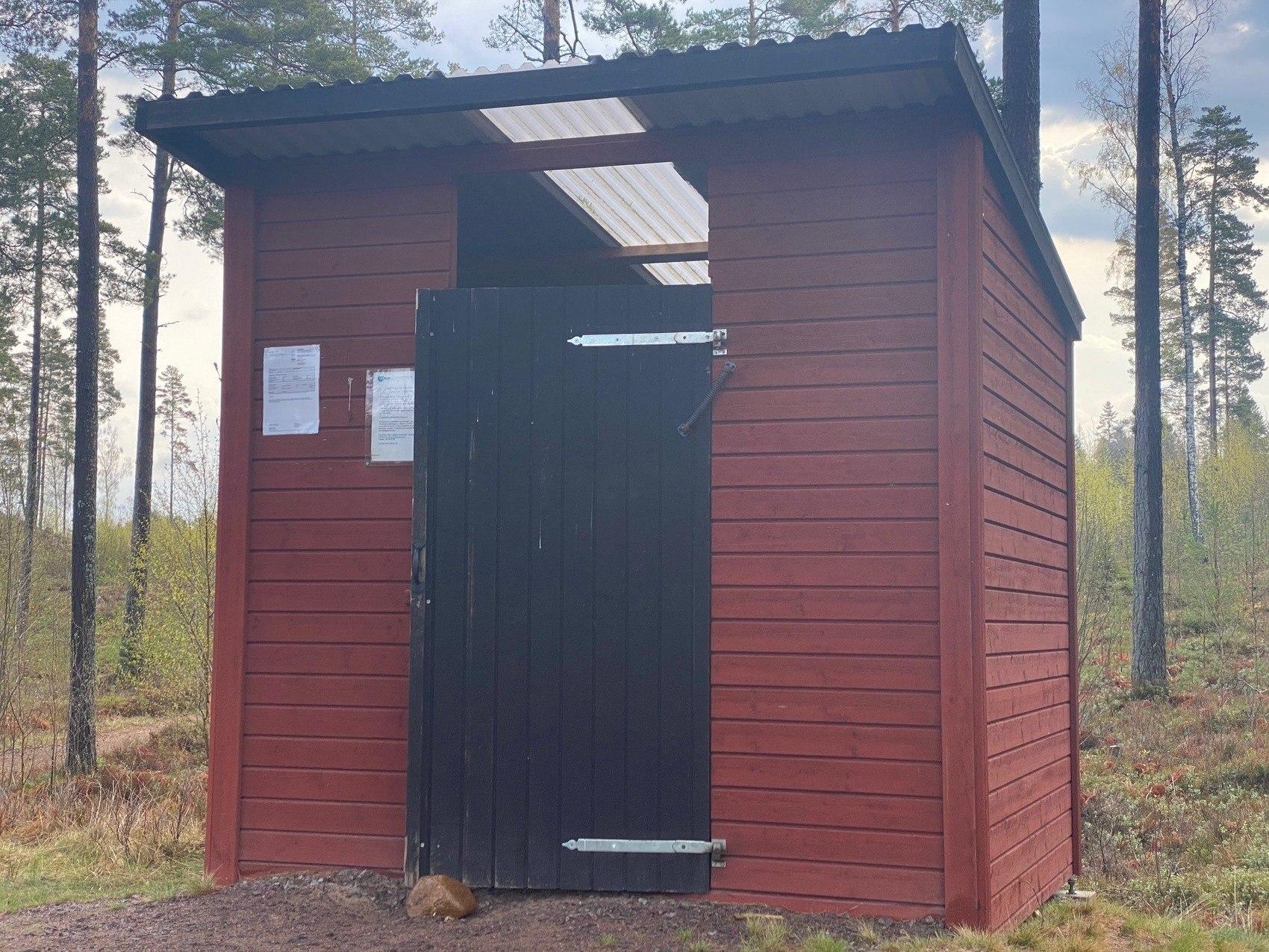 Röd toalettbyggnad