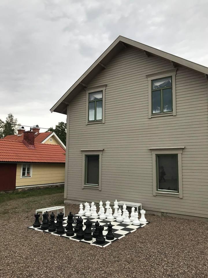 Grå byggnad med ett stort schack utanför