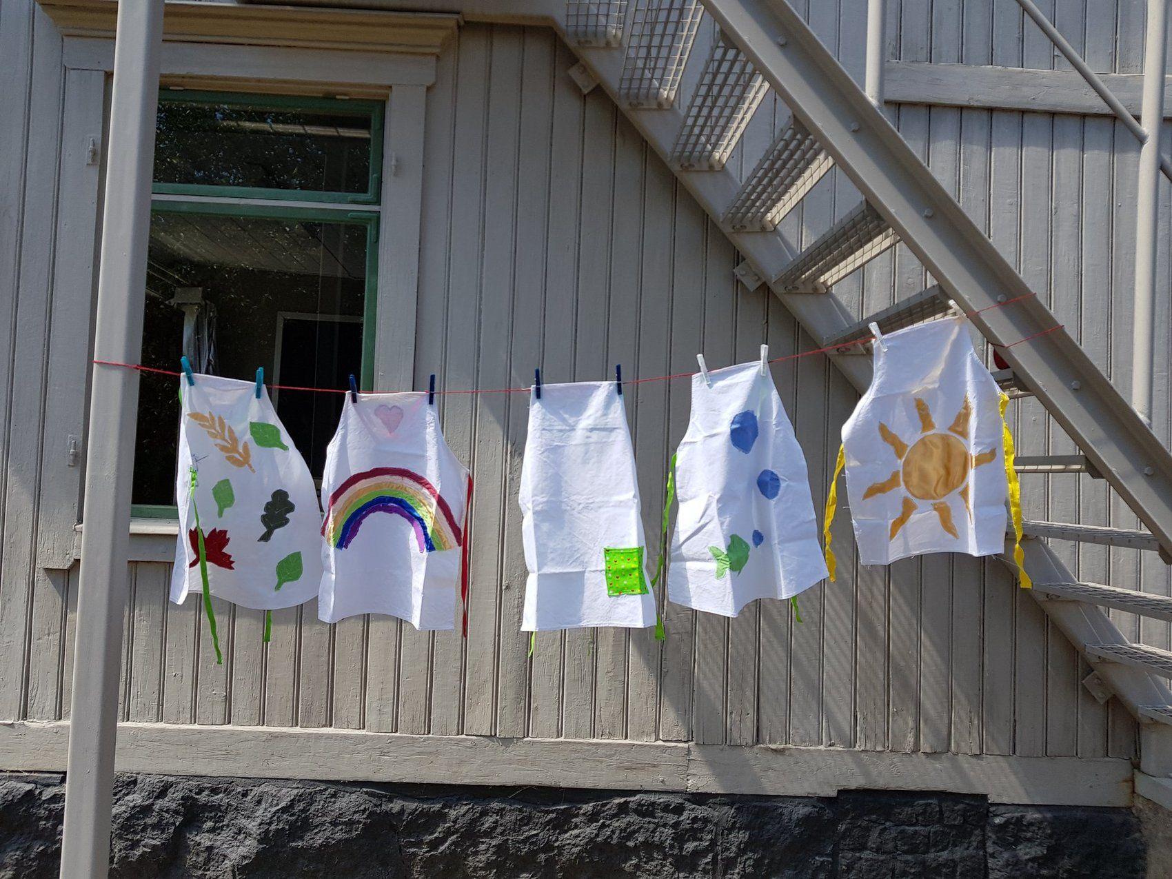 Fem små vita förkläden upphängda på lina