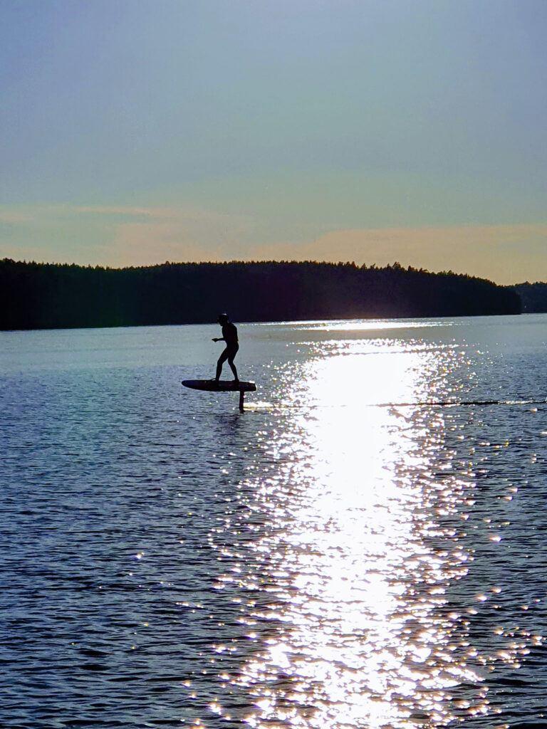 Motljusbild, silhuett av en person som surfar
