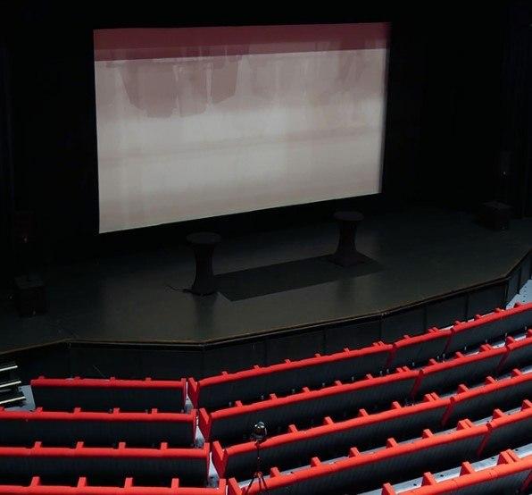 Stor bildskärm framför röda stolar