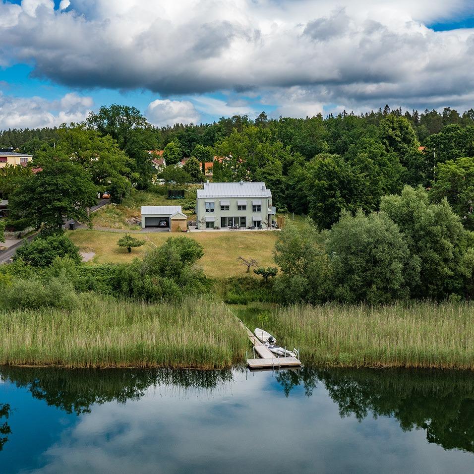 Drönarvy över ett stort vitt hus omgärdat av grönska med vatten i förgrunden där en brygga syns tydligt.