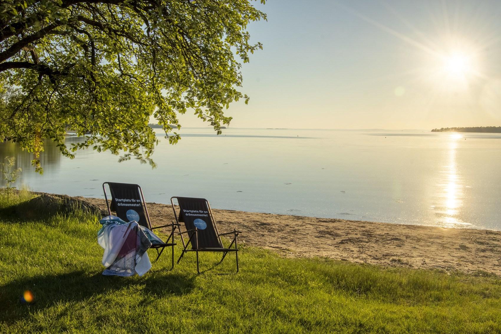 Två svarta solstolar ståendes på en gräsyta under ett stort grönt träd, sandstrand och en stilla sjö i bakgrunden.