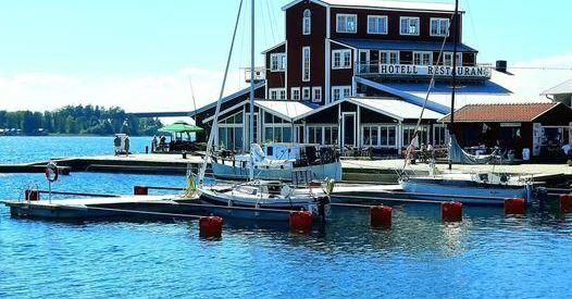 sommarbild på en hamnplats med en förtöjd båt, bakgrunden skymtar en rödvit byggnad