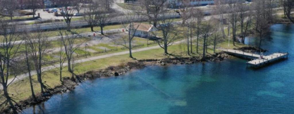 drönarvy över en gräsmatta samt blått vatten, till höger skymtar en brygga.