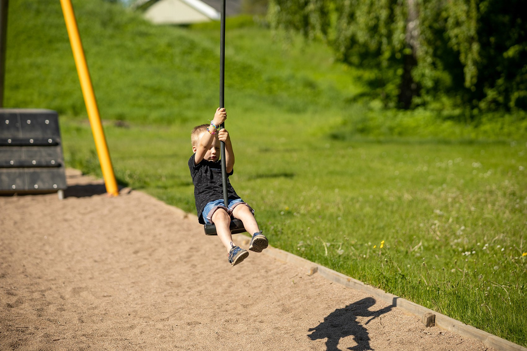 En liten pojke klädd i svart tröja och jeansshorts åker linbana