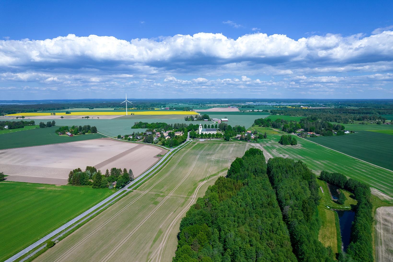 Milsvidd vy över en landsbygd sommaritd, blå himmel och grönskande fält