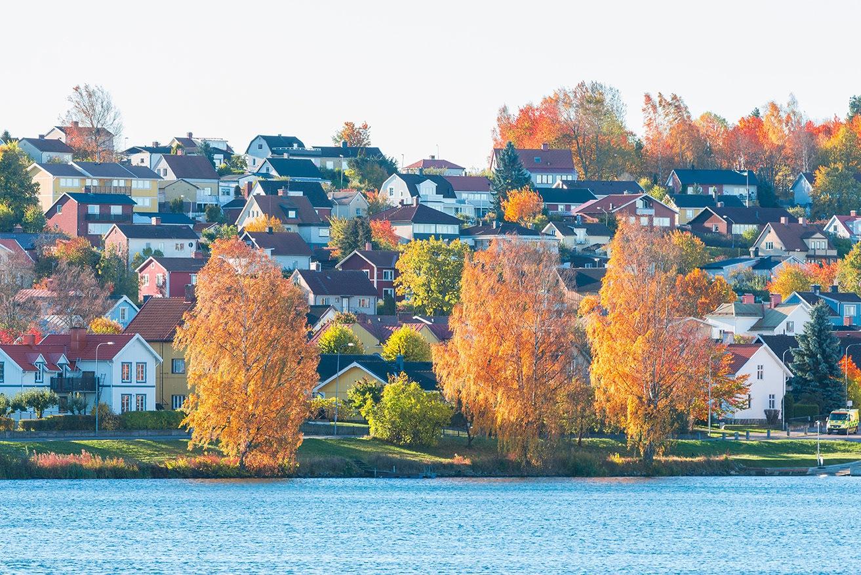 Höstbild på en sjö och massor med hus som ligger i en sluttning
