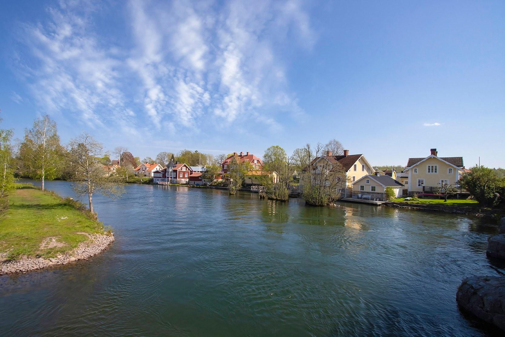 Ett vattendrag som svänger till vänster, intill ligger flera hus