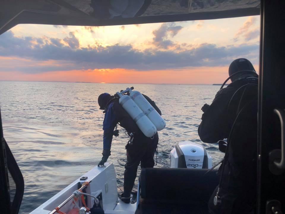 Två dykare på en båt bakifrån