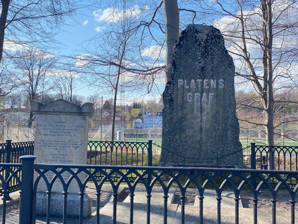 """En väldigt stor gråfärgad gravsten där det står """"Platens graf"""". Runt platsen sår ett metallstaket."""