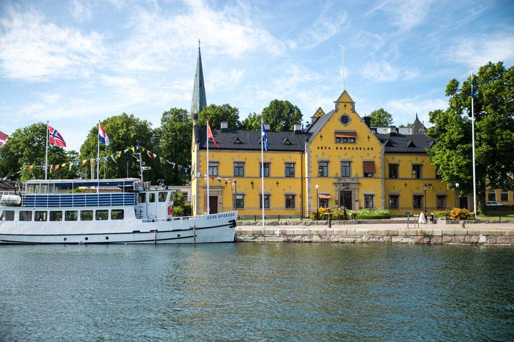 Ett gult stenhus som ligger precis intill vatten, en passagerarbåt passerar framför.