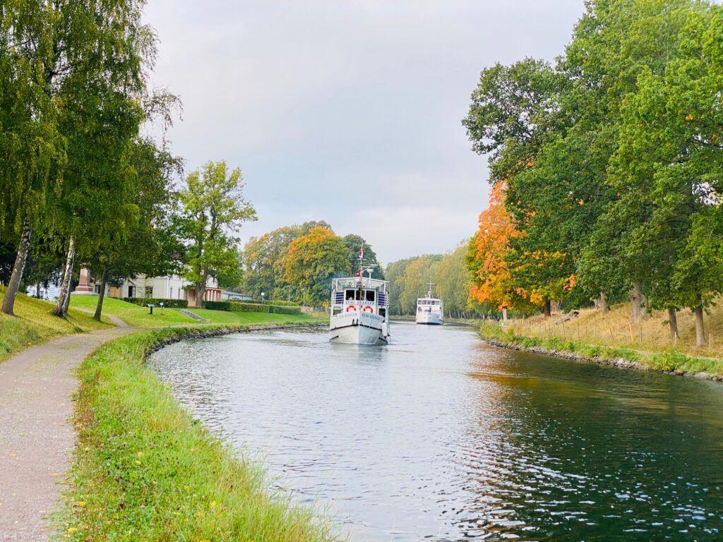 En kanalbåt rör sig framåt i kanalen, höstfärgade träd ramar in bilden