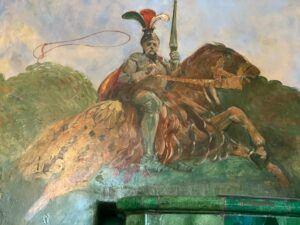 Foto av en målad tavla föreställandes en en man i rustning, ridandes på en häst