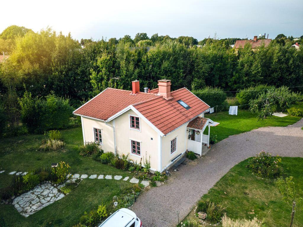 Äldre villa med ljusgul puts och rött tak