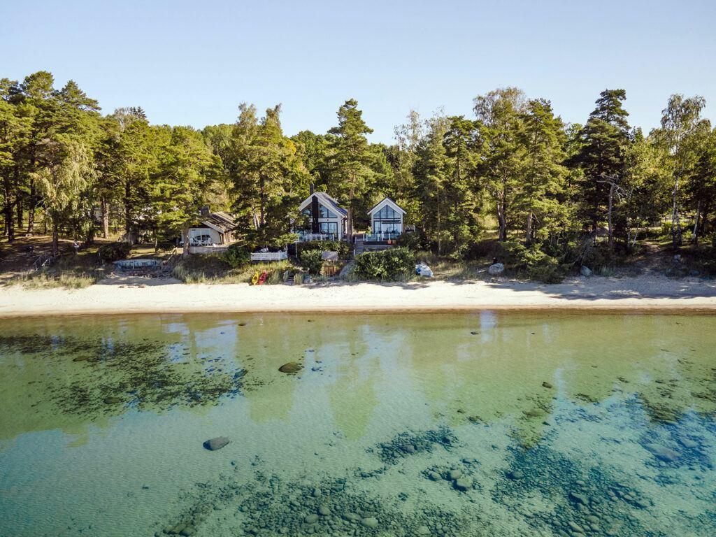 Foto taget från vattnet in mot stranden. Vattnet är kristallklart och på stranden ligger två vita hus.