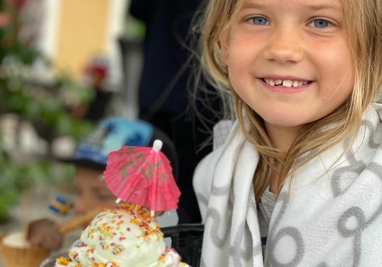 En leende flicka sitter med en glass läckert upplagd i ett högt glas framför sig.