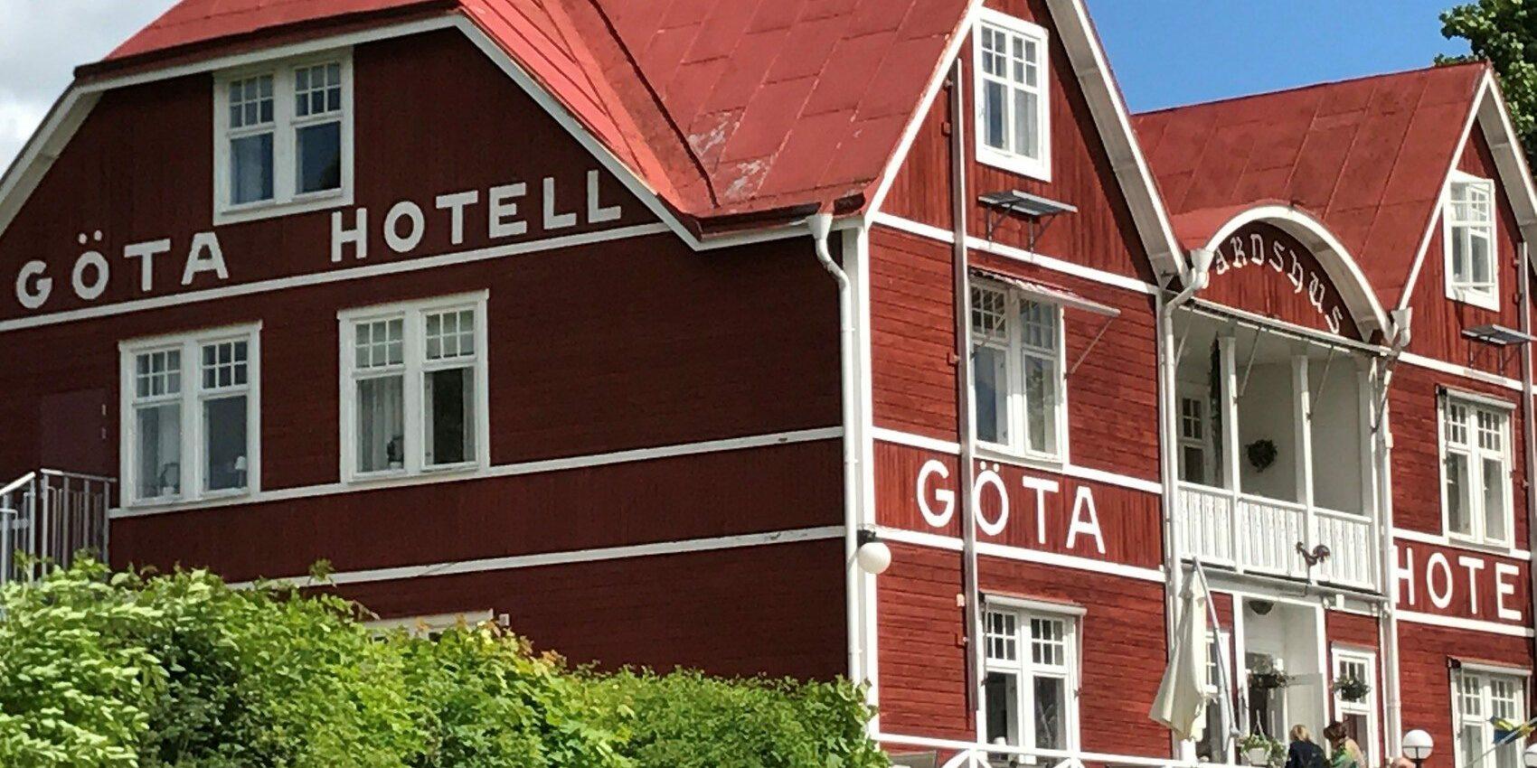 Vacker röd sekelskiftesnyggnad i trä med texten Göta Hotell på gaveln.