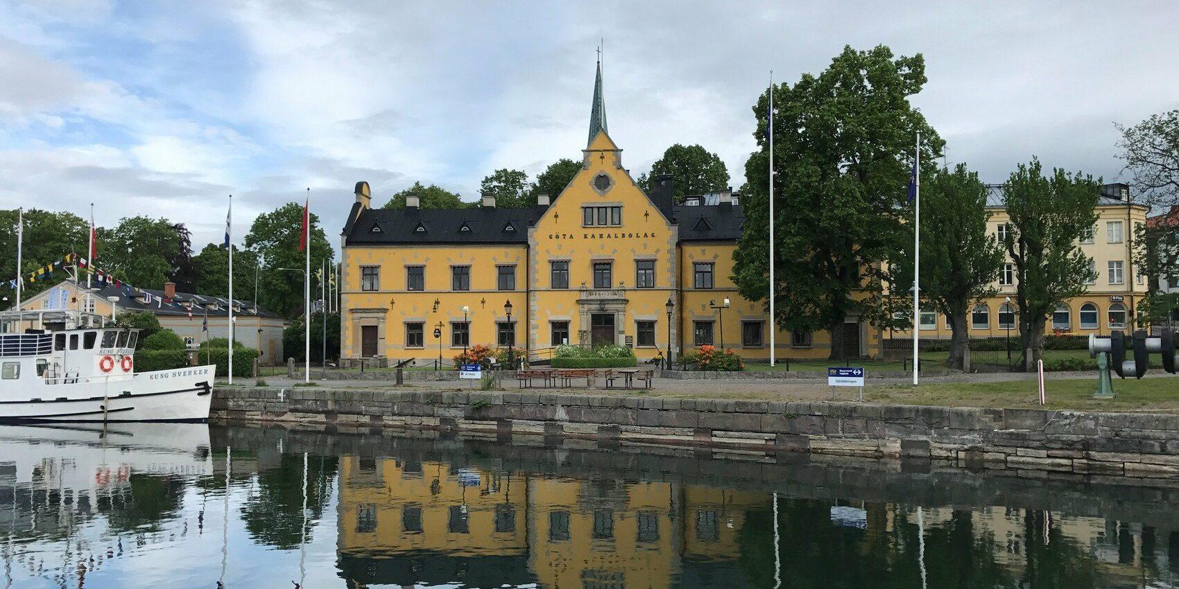 Spegelblankt vatten. På andra sidan vattnet ser man en stor och pampig gul byggnad.