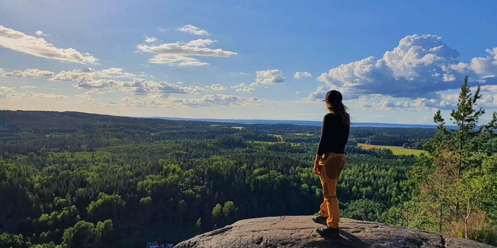 En person i gula friluftsbyxor och keps står på en bergsklippa och tittar ut över en magisk utskikt.