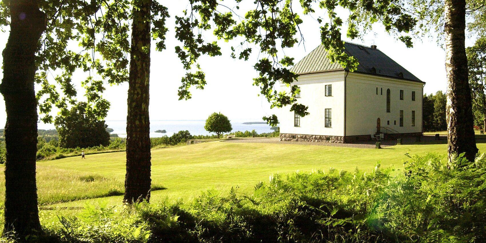 Stort pampigt vitt hus från början av 1900-talet tittar fram mellan träd.