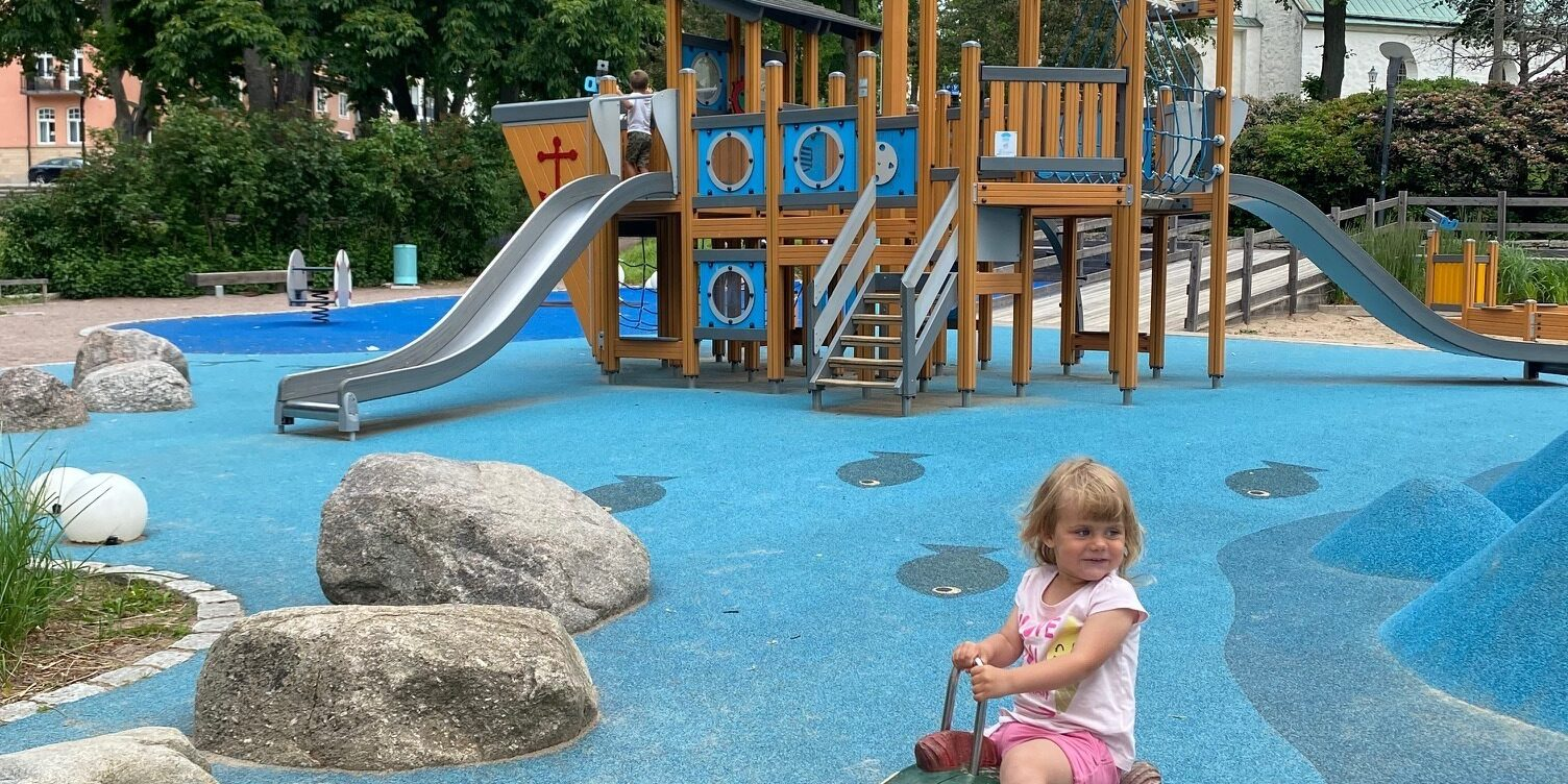 Lekpark med blått underlag. I bakgrunden syns en stor klätterställning och i förgrunden sitter en flicka och gungar på en figur.