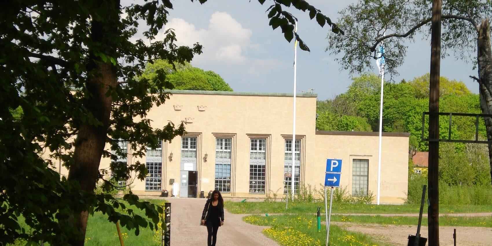 Fot taget från långt håll på en vit byggnad, en silhuett av en gående person syns framför byggnaden.