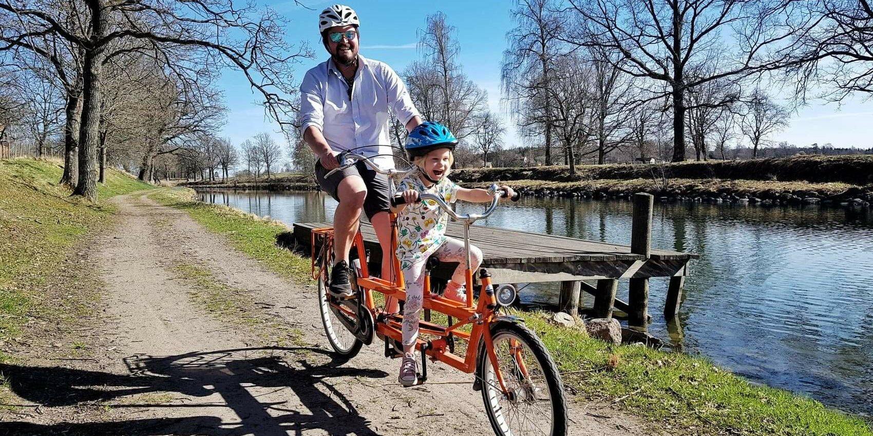 En man cyklar med ett barn på en orange tandemcykel längs md en kanal