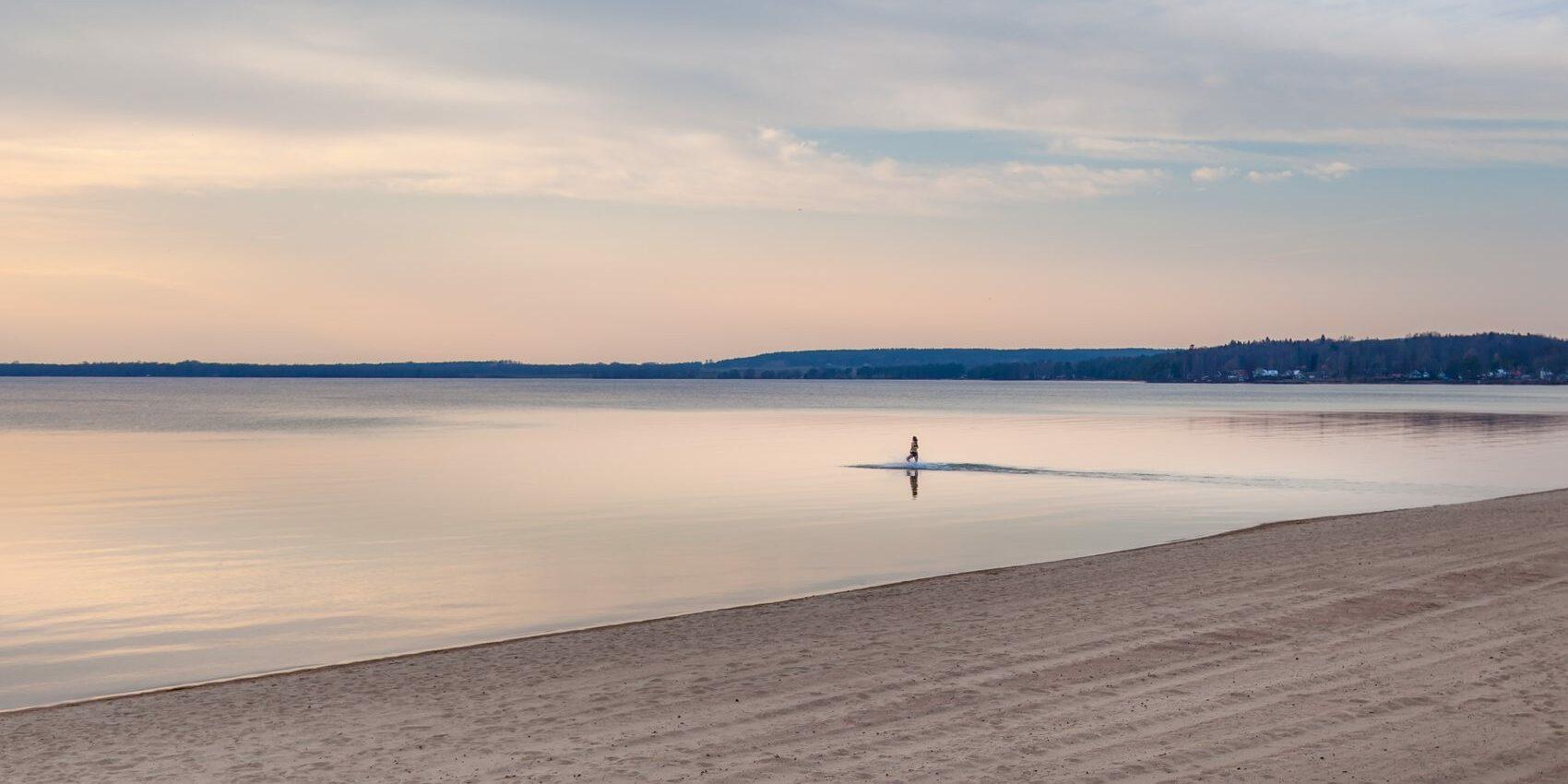 Skyning över en sandstrand med helt stilla vatten. En person badar i vattnet.